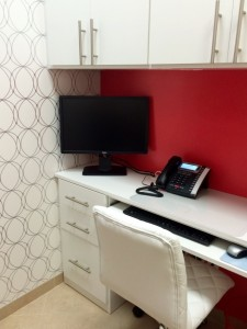Home office, symmetry closets, custom desk, red paint, office computer, office phone, white hciar, white office, white desk