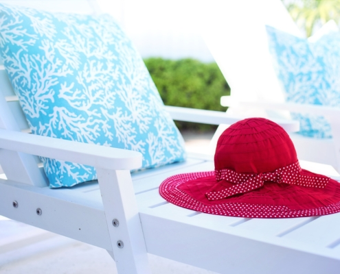 White Lounge Chair with Blue and white pillow and red sunhat, outdoors
